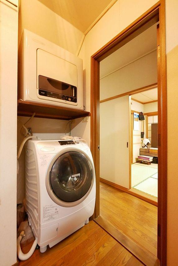 食品庫として使っている納戸が昔はお風呂だったので、キッチンの後ろに洗濯機置場があります。